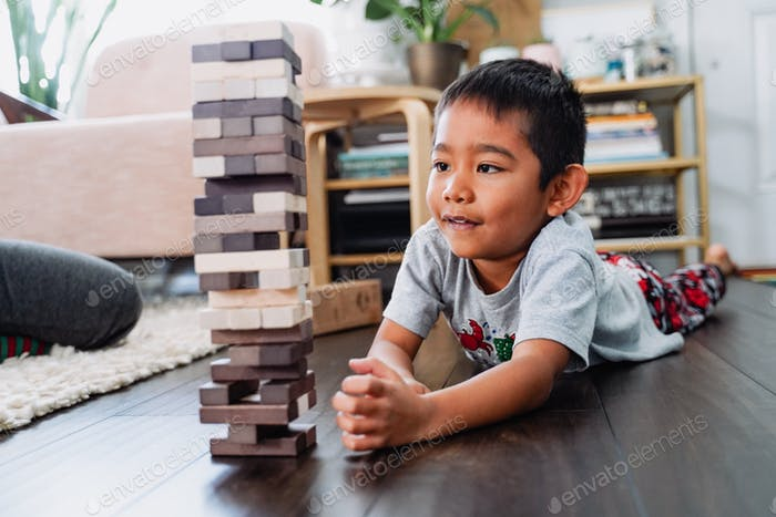 Diverse young little boy playing board game at home distance learning childhood memories unplugged