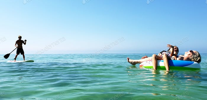 Lazy baby boomer grandma with girl grandkid on a float in the open seas hoping for Prince Charming