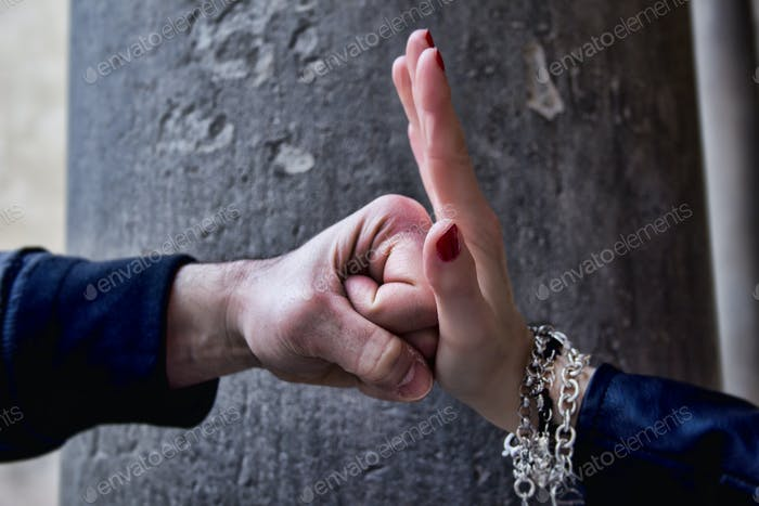 Woman hand stopping  fist of a man . Against violence.