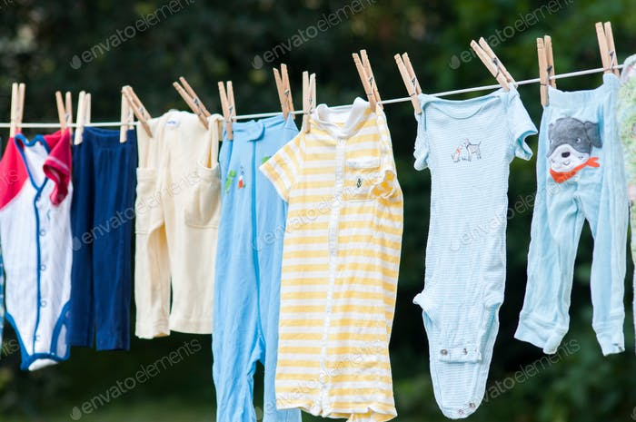 Baby clothes laundry drying outside on the clothesline with clothespins