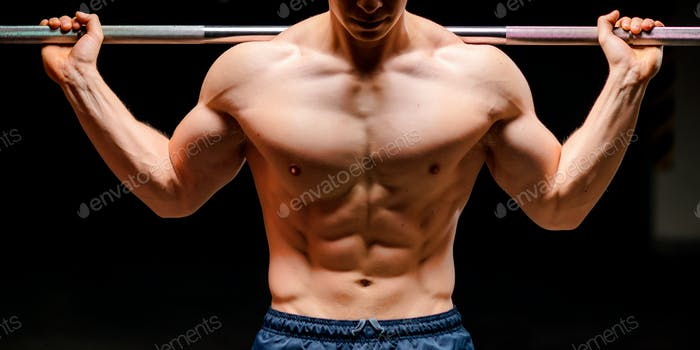 Man's chest. Training in a gym.