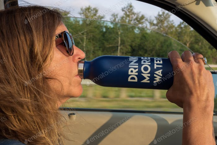 Woman drinking water from a water bottle while driving