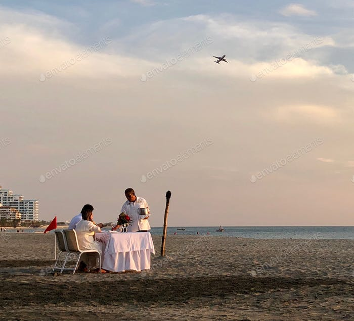 Cute Hispanic Latino couple having a romantic engagement dinner at the beach during the sunset