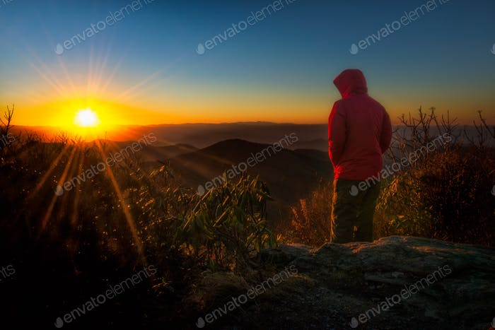 An adventurer braves the winter cold to enjoy a cloudless sunset over the Blue Ridge Mountains.