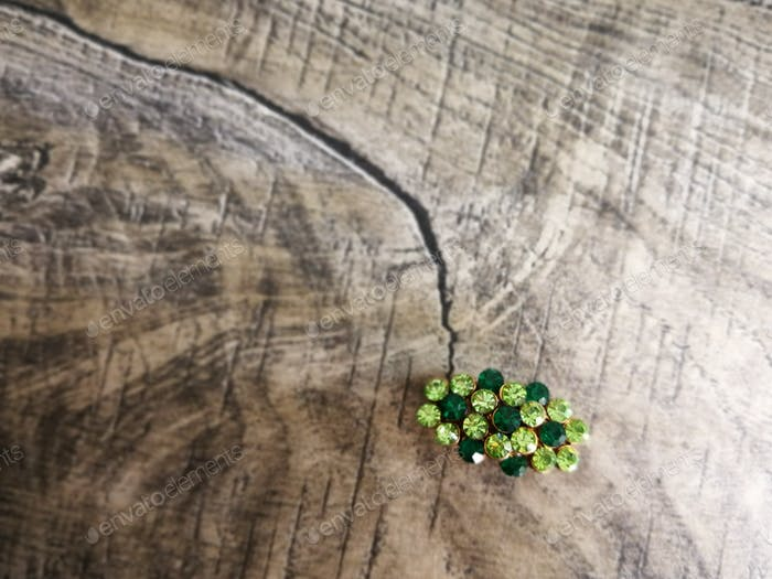 Brooch in green gemstone for clothes isolated on wooden background.