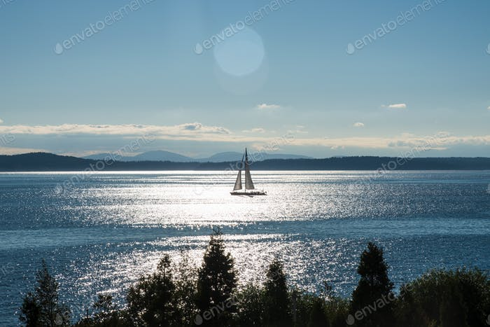 Distant silhouetted sailboat sailing under solar lens flare sun rays.