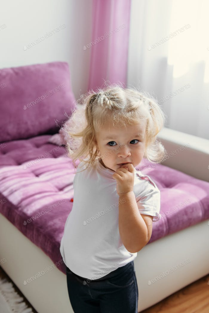surprised small toddler girl dreaming at home. Portrait of young Caucasian baby over pink sofa