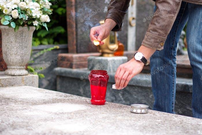 Mittelteil des Menschen, der Kerze auf dem Friedhof anzündet