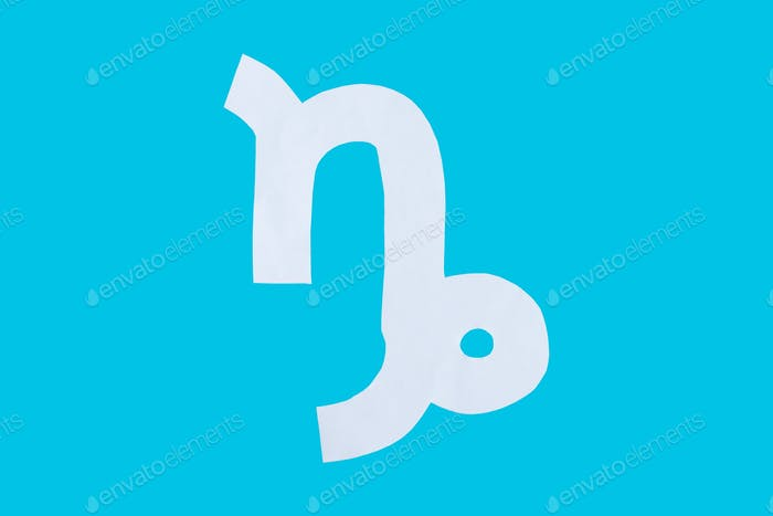 paper cut horoscope sign Capricorn isolated on a blue background