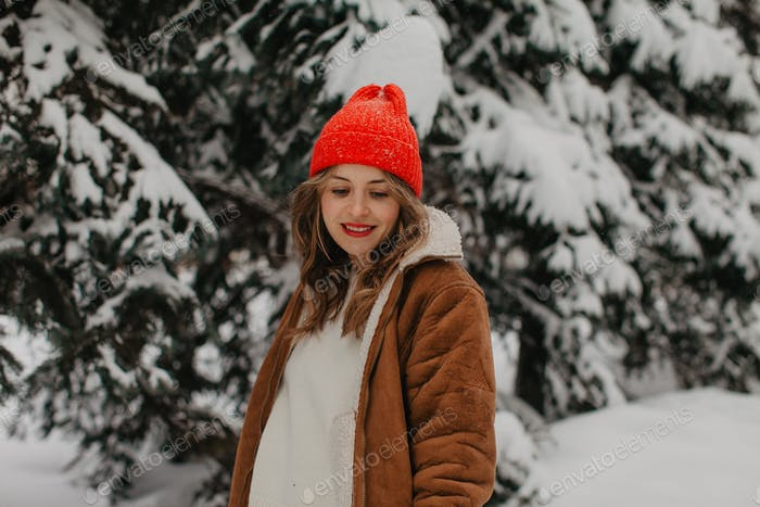 Pretty woman with red hat  in winter forest