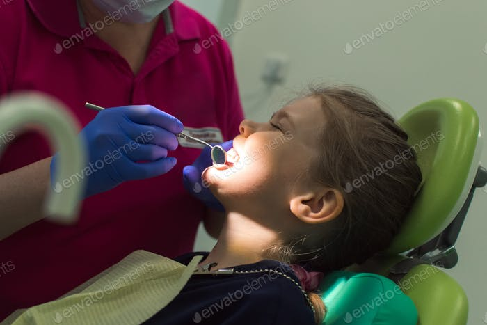 child is being examined by an orthodontist