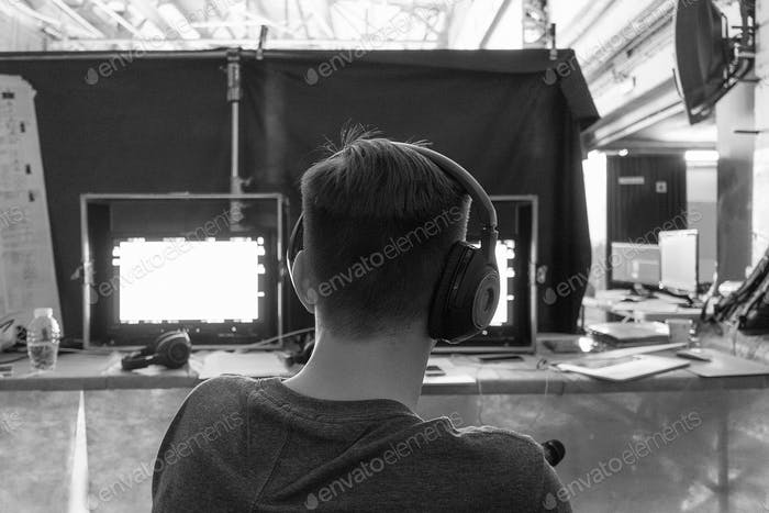 Filmregisseur mit Kopfhörern vor Monitoren