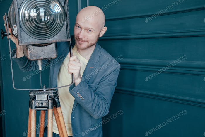 Attractive adult bald man with beard in suit looking at old lighting fixture, video light