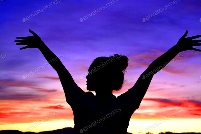 Female holding hands in the air at sunset. Triumph, freedom, rejoicing, victory, happy, joy