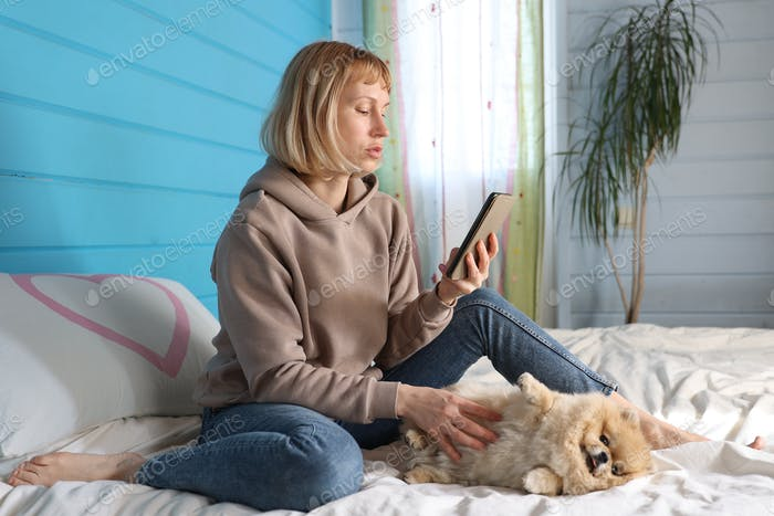 Woman takes selfie with her little dog on bed in bedroom