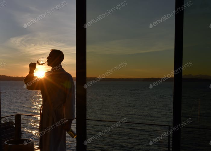 Man at sunset drinking glass of wine