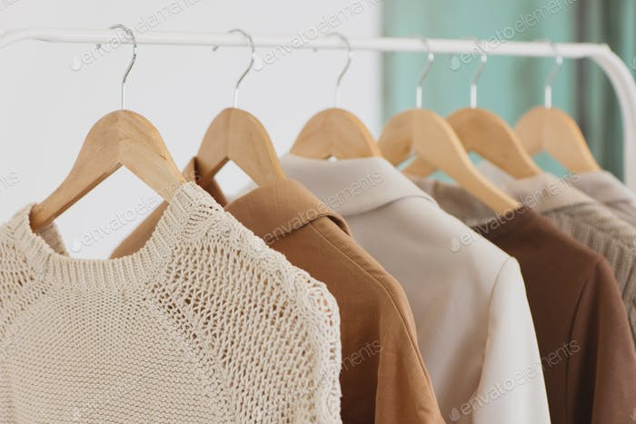 Closeup photo of hangers in clothing rack.