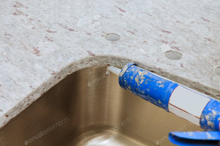 Gun putting silicone sealant to installing a kitchen sink with modern decorative granite countertops