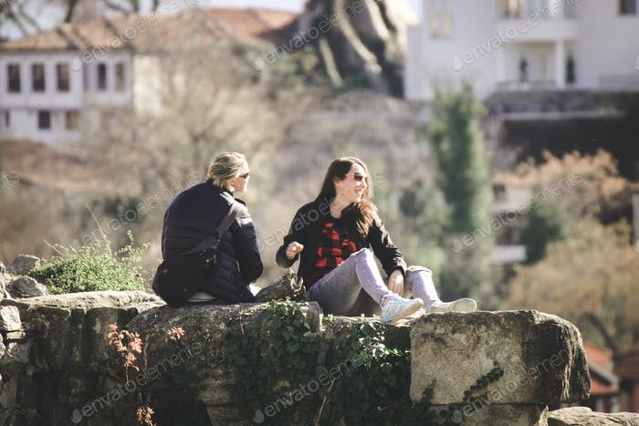 Friends sitting on a stone of the top of the city