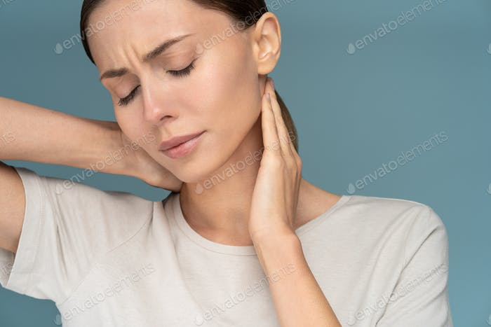 Woman suffering from chronic neck pain, gently massages with hands, having upper back ache