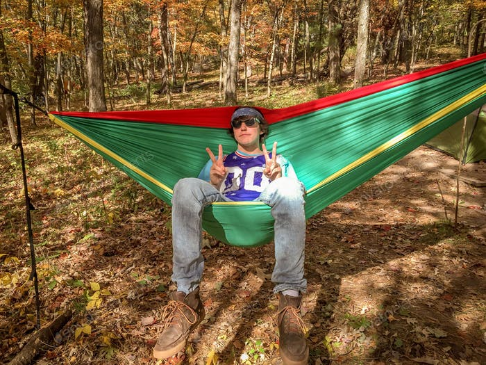 Dude chilling in a hammock flashing peace signs