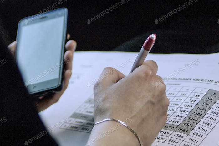 a business woman calculates the financial costs and revenues and making notes in Notepad