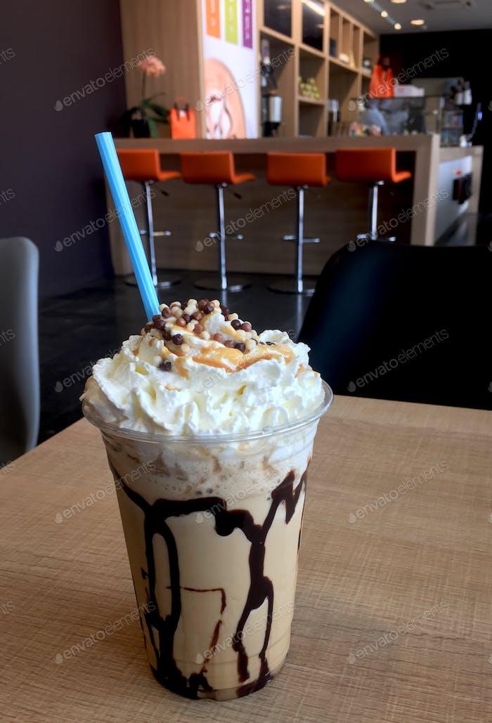 Iced Caramel Caffee Frappé Getränk mit einem Strohhalm im Coffeeshop