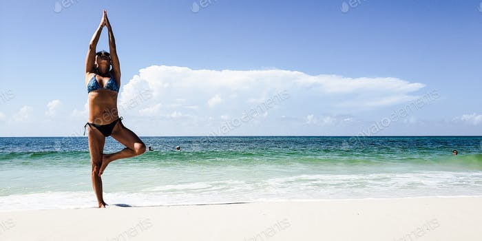 Millenial woman doing yoga on the beach as part of her daily routine in fitness...