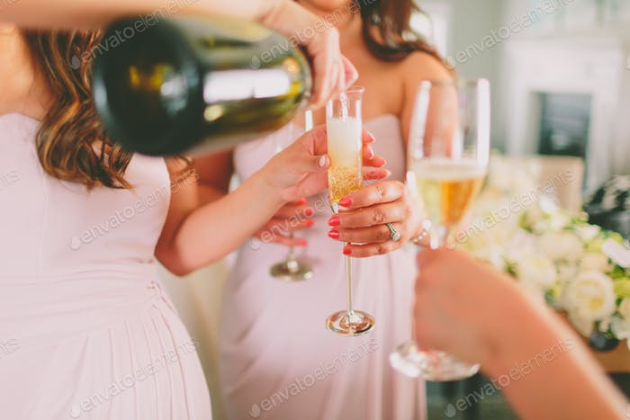 Bridesmaids pouring champagne for a celebratory cheers.