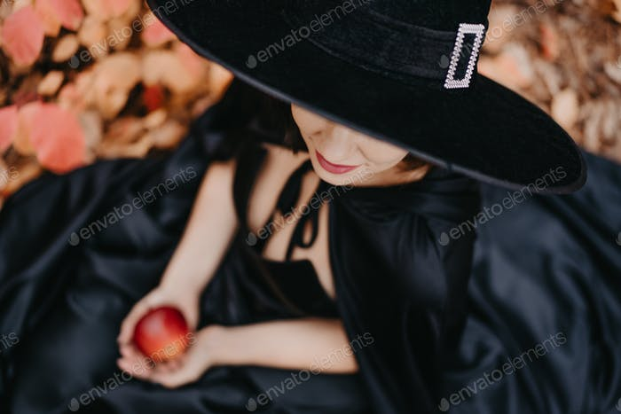 Unrecognizable girl as witch in black hat holding red apple as symbol of temptation, poison