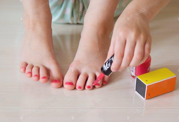 girl paint his nails bright varnish