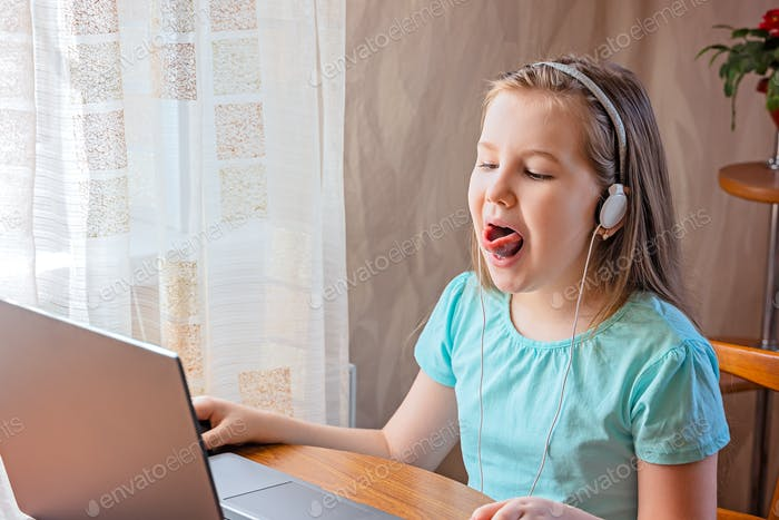 Speech training concept. Little girl uses a laptop to study at home with a teacher, a speech therapi