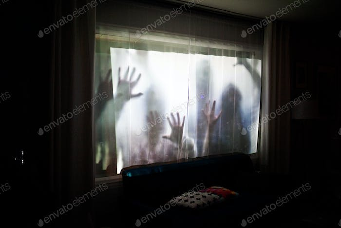 zombies projected on window for halloween