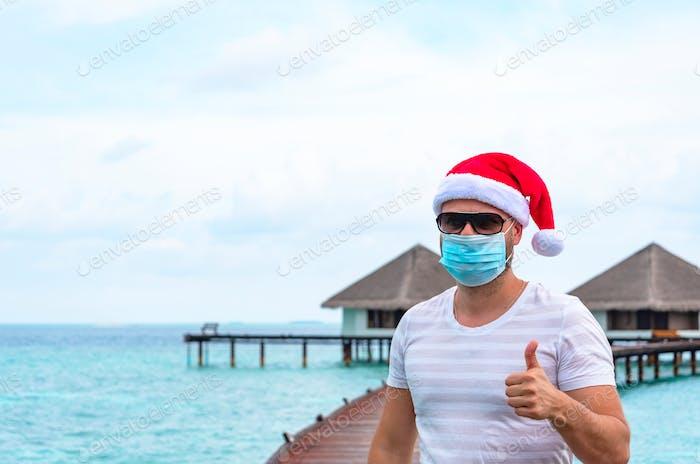 ein junger Mann mit Schutzmaske und Weihnachtsmütze steht auf einem Pier in der Nähe von Wasservillen