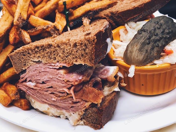 Reuben Sandwichplatte mit Pommes Frites, Krautsalat und einer Essiggurke