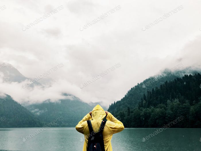 A man in a yellow cloak stands with his back in nature near the lake, the background of beautiful mo