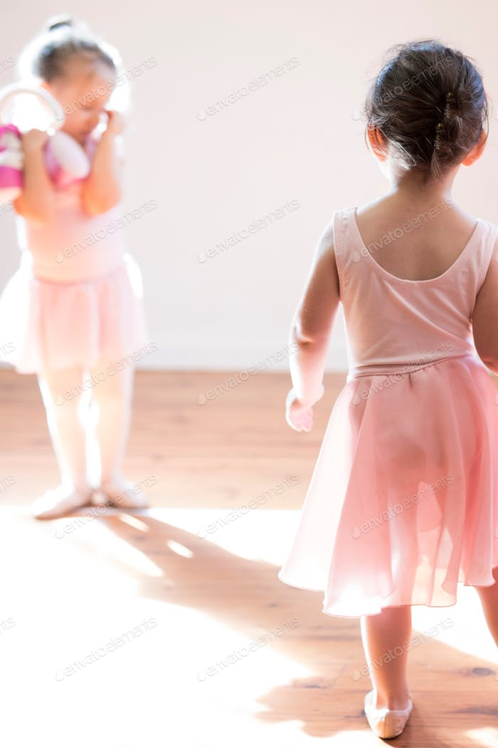 Two little girl toddler ballerinas in pale pink leotards, tutus and ballet shoes dancing together in