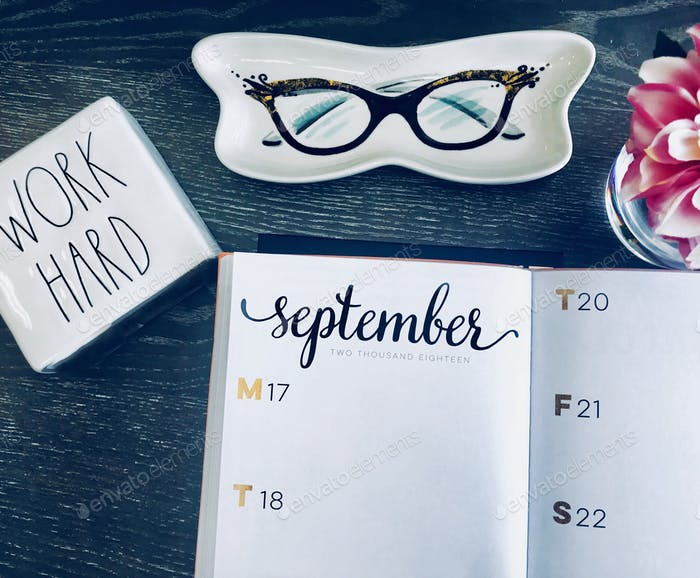 A desk overhead with calendar that reads September
