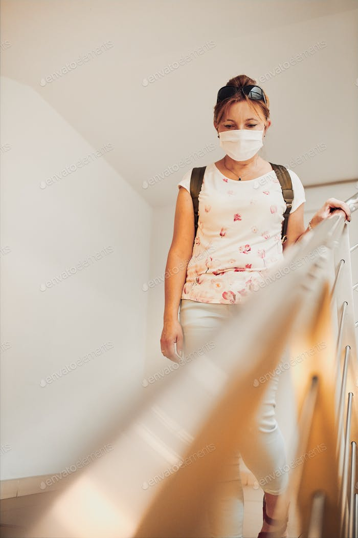Woman going downstairs in public place inside wearing face mask to cover mouth and nose
