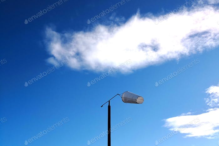 Wind direction indicator. Windsock on blue sky as background. East wind.