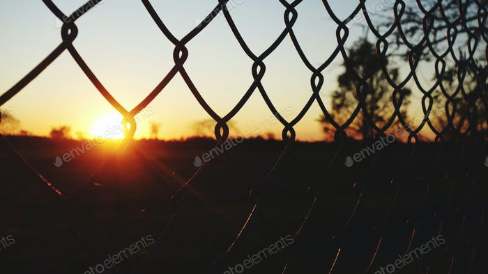 The Sun Touching Down At Sunset Behind A Chainlink Fence