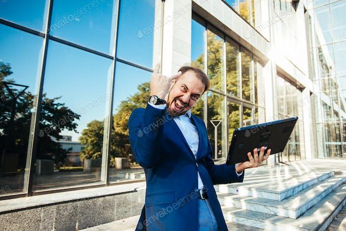 Successful businessman dancing and celebrating triumph