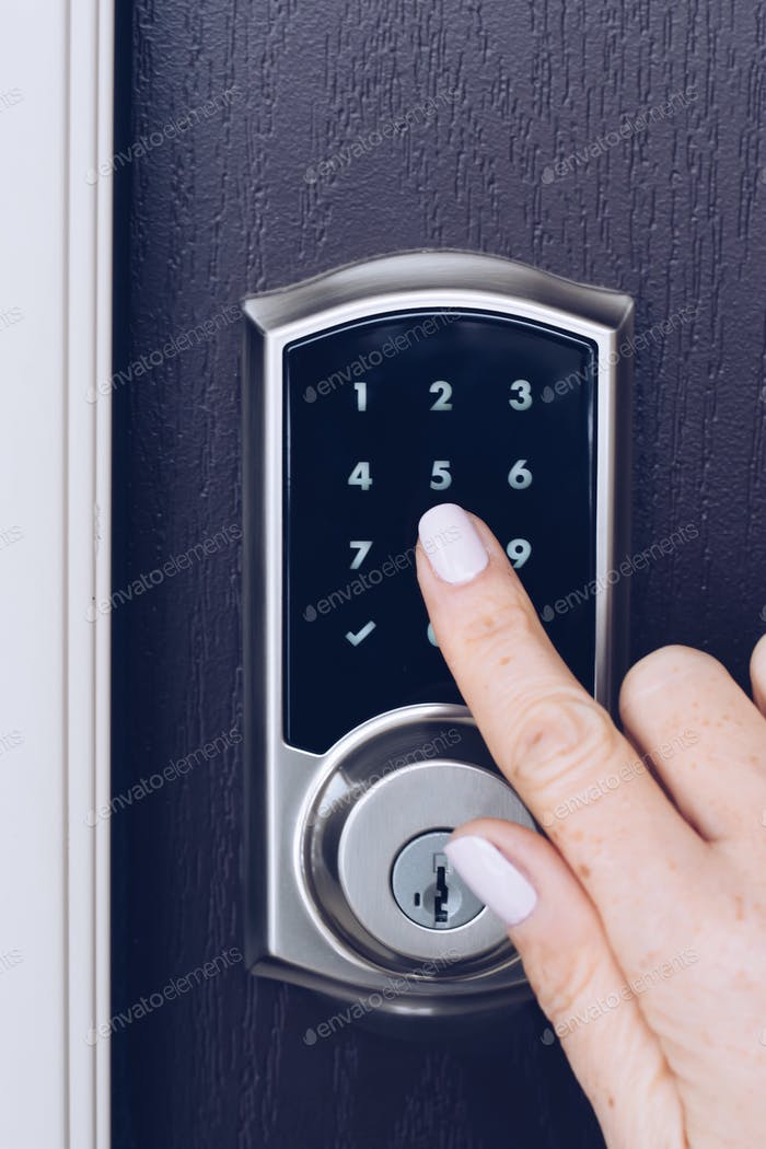 Woman's hand is pressing numbers on an electronic keypad to open the door of a house
