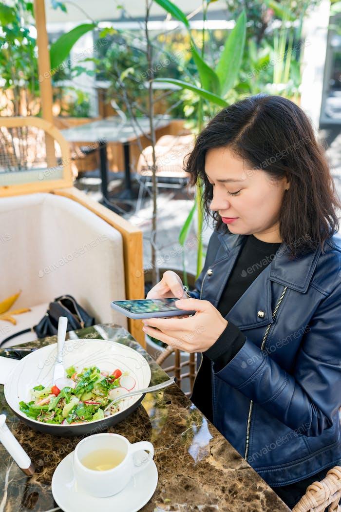 Mujer joven linda en ropa casual sentada en la cafetería al aire libre en el día soleado usando el teléfono inteligente.