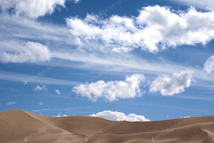 Pale blue sky over sand dunes