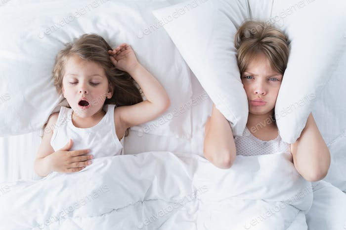 Little girls sleep in bed. One is snoring hard, sister is plugging her ears with pillow. Early morni