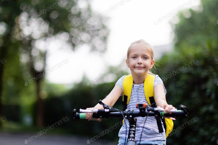 Schoolgirl back to school after summer vacations. Child riding on bicycle on road