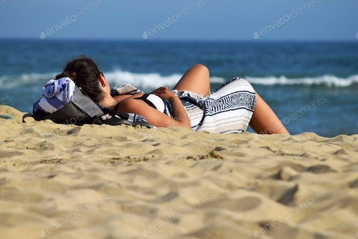 Woman relaxing on South Beach, Martha's Vineyard, Massachusetts off the coast of Cape Cod