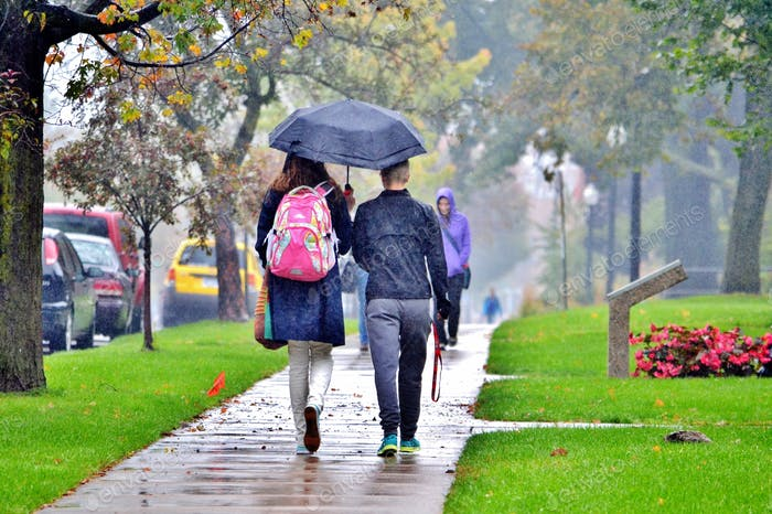 College students walking to class on a rainy day in Spring! April showers bring May flowers!