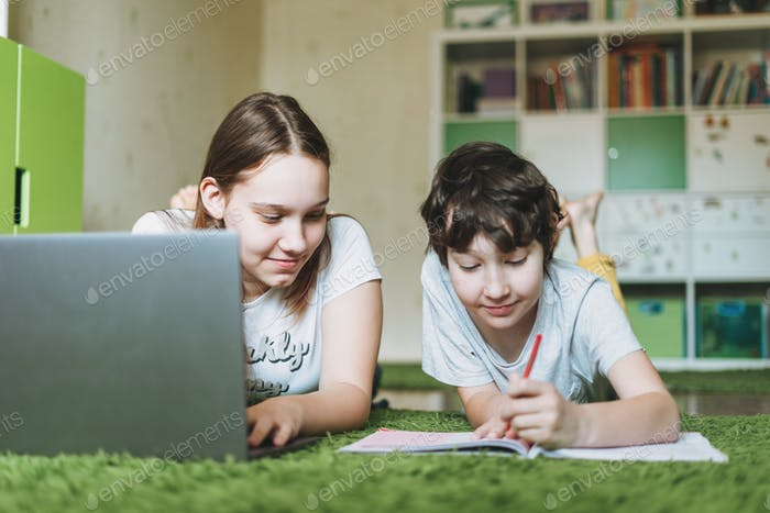 Siblings brother sister attractive girl teenager and tween boy do homework learn foreign language